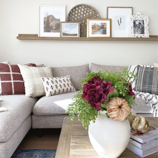 A living room seating area styled with fall decor and pillows.